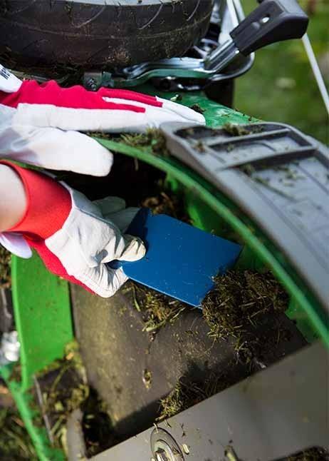 Den Rasenmäher mit einer Spachtel reinigen